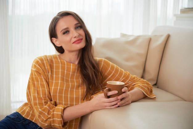 Ritratto di bella donna seduta sul pavimento al divano con tè caldo e sorridente