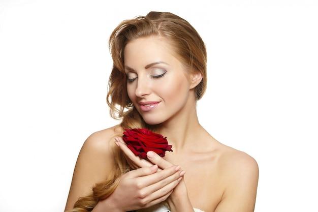Ritratto di bella donna sensuale con la rosa rossa su bianco