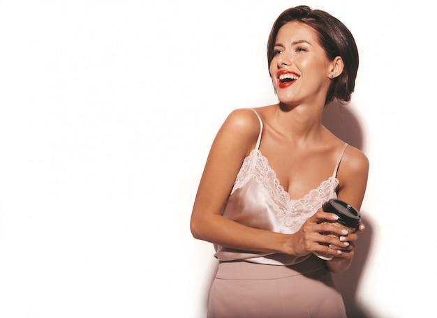 Ritratto di bella donna sensuale del brunette. ragazza in eleganti abiti classici beige e pantaloni larghi. tazza da caffè in plastica di modello