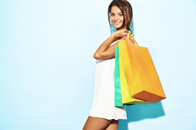 Ritratto di bella donna shopaholic sorridente che tiene i sacchi di carta variopinti. donna castana che posa sulla parete blu dopo la compera. modello positivo