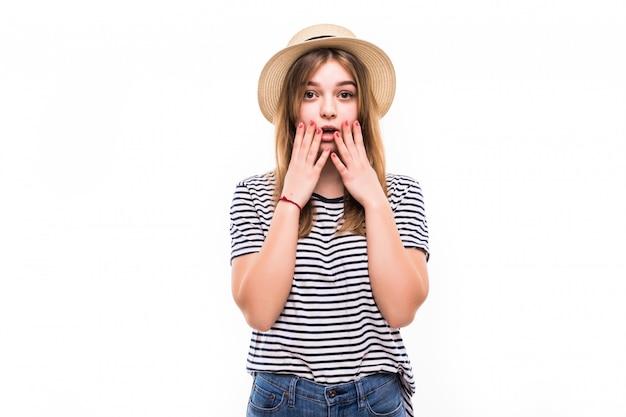 Ritratto di bella donna sorpresa che tiene la testa con stupore e bocca aperta sopra il muro bianco