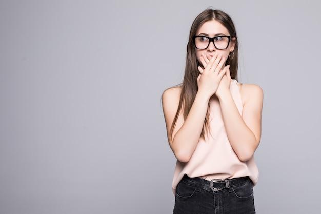 Ritratto di bella donna sorpresa che tiene la testa stupita e a bocca aperta sul muro bianco