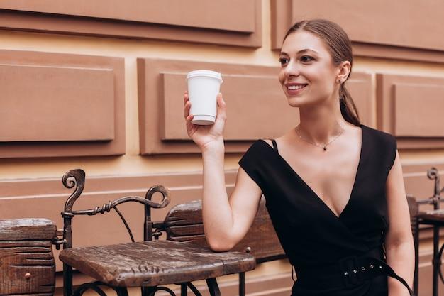 Ritratto di bella donna sorridente che gode del tempo libero mentre sedendosi nel terrazzo esteriore della caffetteria
