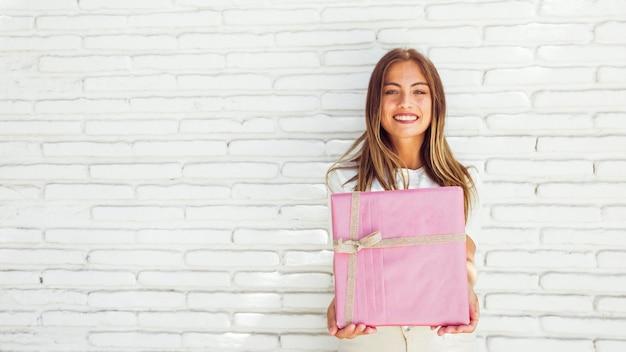 Ritratto di bella donna sorridente che tiene il contenitore di regalo rosa contro il muro di mattoni