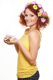 Ritratto di bella donna sorridente dello zenzero di redhead in panno giallo con i fiori variopinti rosa gialli in capelli isolati sui fiori bianchi della tenuta