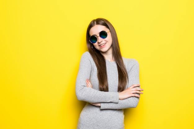 Ritratto di bella donna sorridente in occhiali da sole e vestito contro della parete gialla