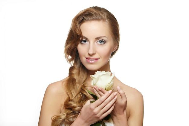 Ritratto di bella donna sorridente sensuale con la rosa di bianco su bianco