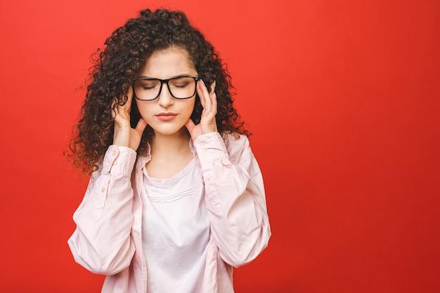 Ritratto di bella donna studente stanco al lavoro, isolato su uno sfondo rosso.