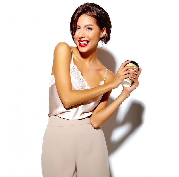 Ritratto di bella felice carina donna bruna sexy con le labbra rosse in pantaloni classici larghi tenendo tazza di caffè in plastica su sfondo bianco