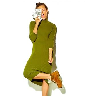 Ritratto di bella felice carina ragazza sorridente donna bruna in abiti casual casual verde estate hipster isolato su bianco azienda banconota da un dollaro vicino al viso
