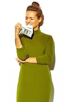 Ritratto di bella felice carina ragazza sorridente donna bruna in abiti casual casual verde estate pantaloni a vita bassa isolato su bianco azienda banconota da un dollaro in bocca