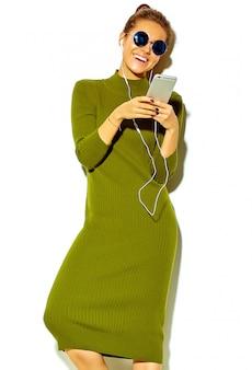 Ritratto di bella felice carina ragazza sorridente donna bruna in abiti casual estate verde hipster isolato su bianco in occhiali da sole ascoltando musica in smartphone con le cuffie
