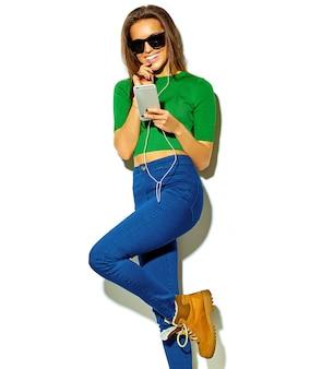 Ritratto di bella felice carina ragazza sorridente donna bruna in abiti casual verde hipster estate senza trucco isolata on white in occhiali da sole ascoltando musica in smartphone con le cuffie