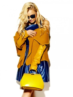Ritratto di bella felice dolce donna bionda donna sorridente in abiti casual maglione caldo hipster casual invernale, con borsa gialla in occhiali da sole