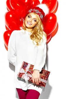 Ritratto di bella felice dolce donna bionda sorridente ragazza con in mano grande confezione regalo di natale e palloncini a cuore in abiti invernali casual rosso hipster, in maglione bianco caldo