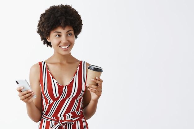 Ritratto di bella femmina afroamericana girly con acconciatura riccia che tiene tazza di caffè e smartphone guardando a destra con un sorriso carino