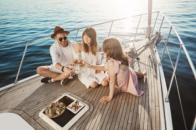 Ritratto di bella gente europea alla moda pranzando a bordo dell'yacht, bevendo vite e godendo dell'estate. tre amici vivono in diversi paesi e finalmente si sono incontrati durante le vacanze