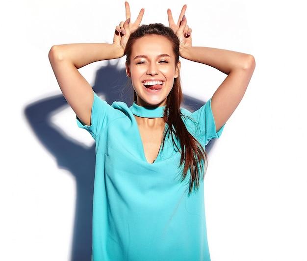 Ritratto di bella giovane donna alla moda che fa le orecchie del coniglietto
