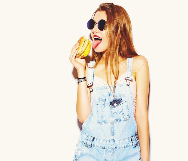 Ritratto di bella giovane donna alla moda che mangia hamburger