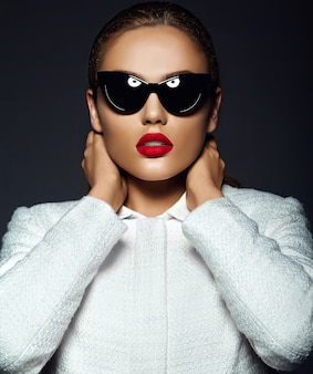 Ritratto di bella giovane donna alla moda con gli occhiali da sole