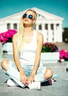 Ritratto di bella giovane donna alla moda con lo skateboard