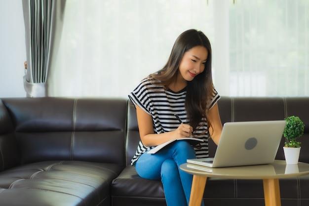 Ritratto di bella giovane donna asiatica che per mezzo del computer portatile sul sofà