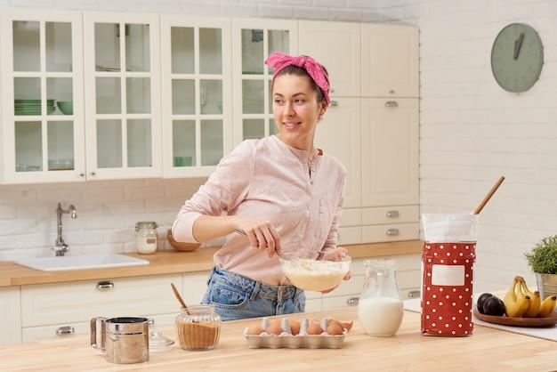 Ritratto di bella giovane donna che mangia prima colazione nella cucina