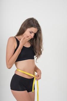 Ritratto di bella giovane donna che misura la sua figura di figura con la misura di nastro