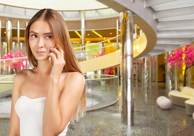 Ritratto di bella giovane donna che per mezzo del telefono cellulare