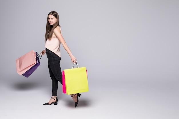 Ritratto di bella giovane donna che posa con i sacchetti della spesa isolati sulla parete bianca