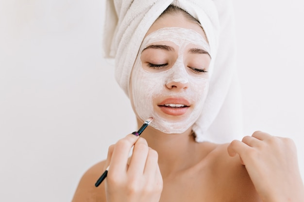 Ritratto di bella giovane donna con asciugamani dopo fare il bagno fa maschera cosmetica sul viso.