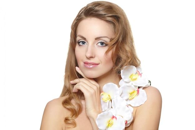 Ritratto di bella giovane donna con il fiore bianco su bianco
