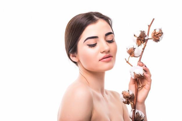Ritratto di bella giovane donna con la pelle di salute e con il fiore sulla sua spalla isolata