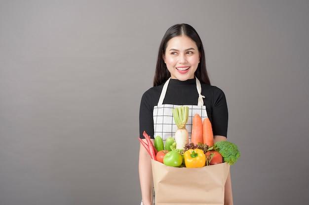Ritratto di bella giovane donna con le verdure nella borsa di drogheria nel fondo di gray dello studio