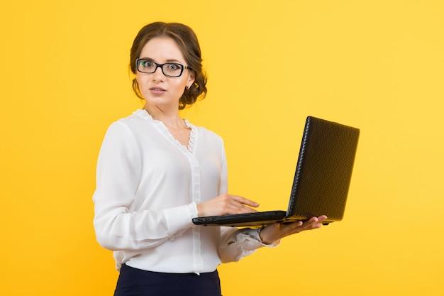 Ritratto di bella giovane donna confusa sicura di affari che lavora al computer portatile su giallo