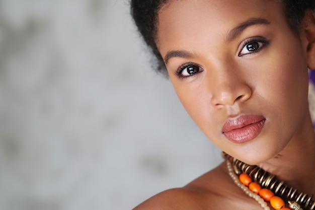 Ritratto di bella giovane donna di colore con la collana africana tradizionale
