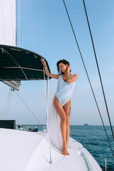Ritratto di bella giovane donna di modo che sta e che posa sulla barca a vela o sull'yacht nel mare che porta costume da bagno bianco moderno