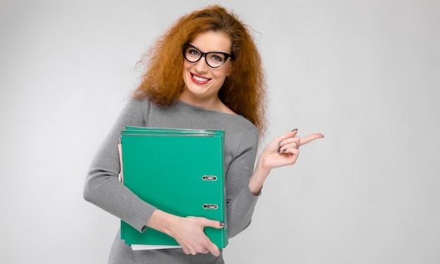 Ritratto di bella giovane donna di redhead in vestiti grigi in vetri che tengono le cartelle sulla parete grigia