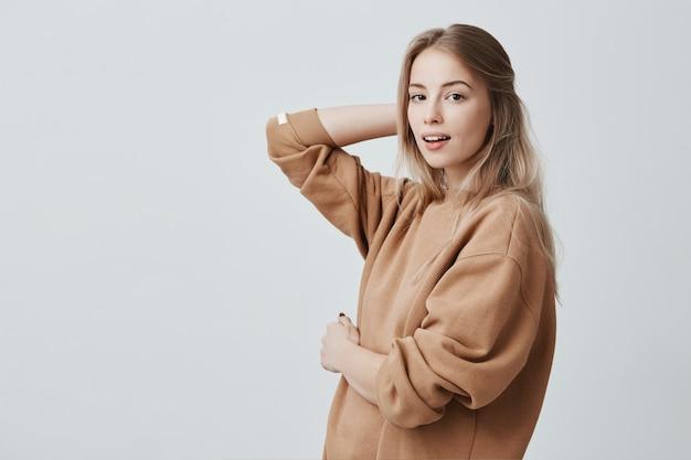 Ritratto di bella giovane donna europea attraente alla moda con gli occhi scuri e capelli biondi lunghi che posano all'interno. modello femminile alla moda isolato