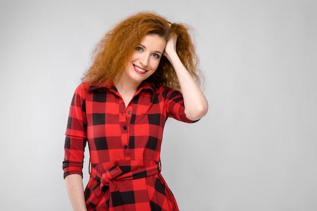 Ritratto di bella giovane donna felice rossa sorridente tenendo la mano sui capelli sul muro grigio