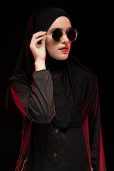 Ritratto di bella giovane donna musulmana alla moda che indossa hijab e gli occhiali da sole neri come concetto orientale moderno di modo che posa sul fondo nero