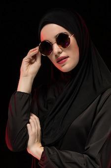 Ritratto di bella giovane donna musulmana alla moda che indossa hijab nero e gli occhiali da sole come concetto orientale moderno di modo che posa il nero