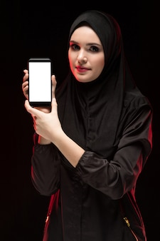 Ritratto di bella giovane donna musulmana astuta che indossa il telefono cellulare nero di pubblicità del hijab in sue mani come il nero di concetto di istruzione