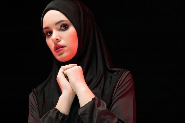 Ritratto di bella giovane donna musulmana seria che indossa hijab nero con la mano a disposizione come concetto pregante sul nero