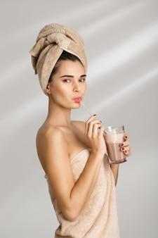 Ritratto di bella giovane donna sciccosa dopo il bagno che sta coperto in asciugamano.