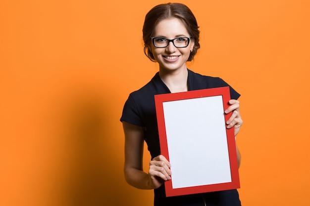 Ritratto di bella giovane donna sicura di affari che tiene la struttura in bianco della foto in sue mani