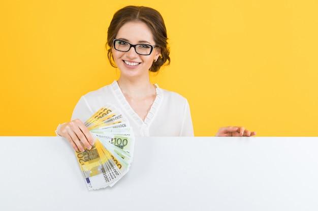 Ritratto di bella giovane donna sicura di affari con soldi in sue mani e tabellone per le affissioni in bianco su giallo