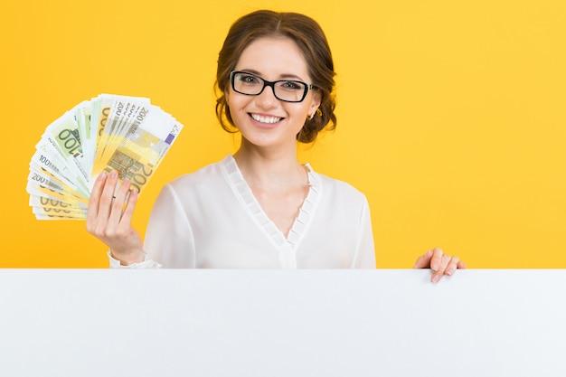 Ritratto di bella giovane donna sicura di affari con soldi in sue mani e tabellone per le affissioni in bianco