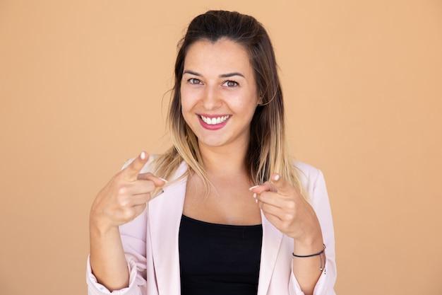 Ritratto di bella giovane donna sorridente che indica la macchina fotografica