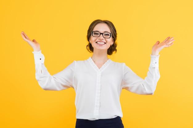 Ritratto di bella giovane donna sorridente felice di affari fiducioso su giallo